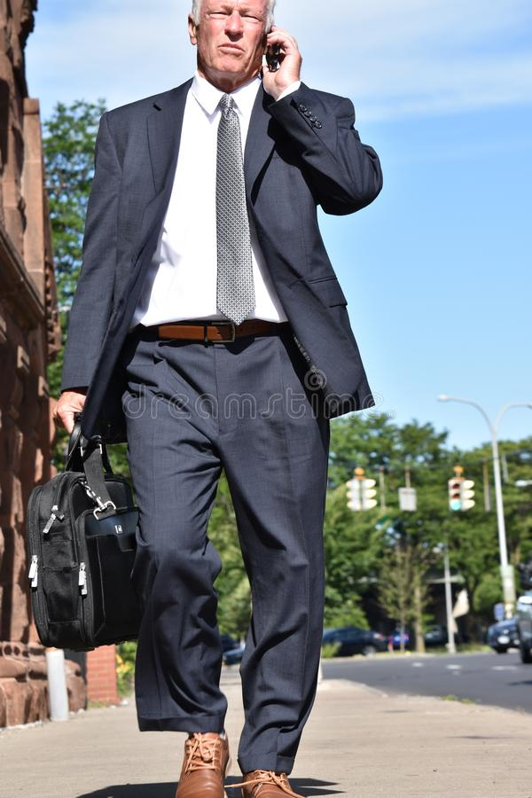 El caminar del traje y del lazo de Using Cell Phone del empresario que lleva fotografía de archivo libre de regalías