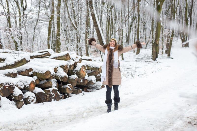 El caminar hermoso de la mujer joven feliz en el más forrest en un invierno d fotos de archivo