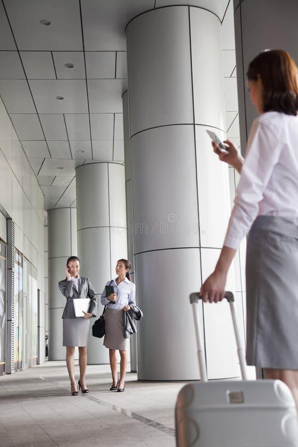 El caminar joven de tres empresarias exterior y el hablar en el teléfono fotografía de archivo