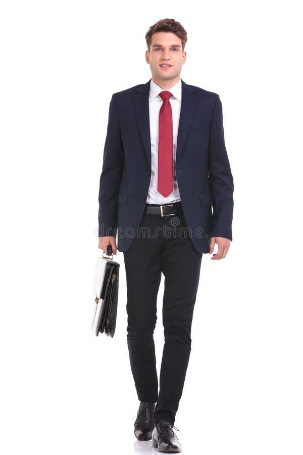 El caminar joven sonriente del hombre de negocios foto de archivo libre de regalías