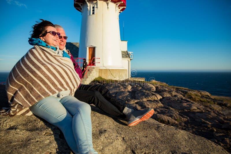 El caminar maduro de amor de los pares, sentándose en el top ventoso de la roca imágenes de archivo libres de regalías