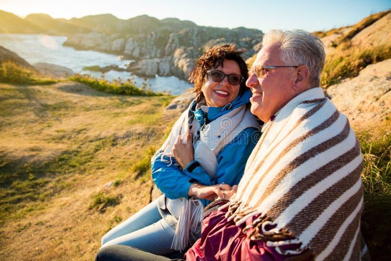 El caminar maduro de amor de los pares, sentándose en el top ventoso de la roca imagen de archivo