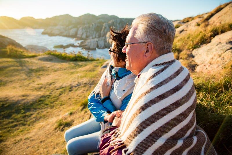 El caminar maduro de amor de los pares, sentándose en el top ventoso de la roca foto de archivo