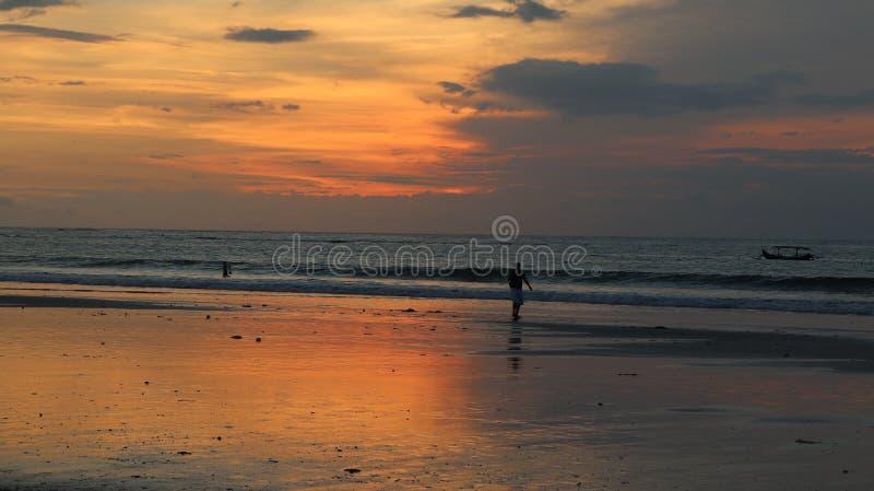 El caminar masculino en la orilla de la playa y un niño que juega en el agua en la puesta del sol imagen de archivo