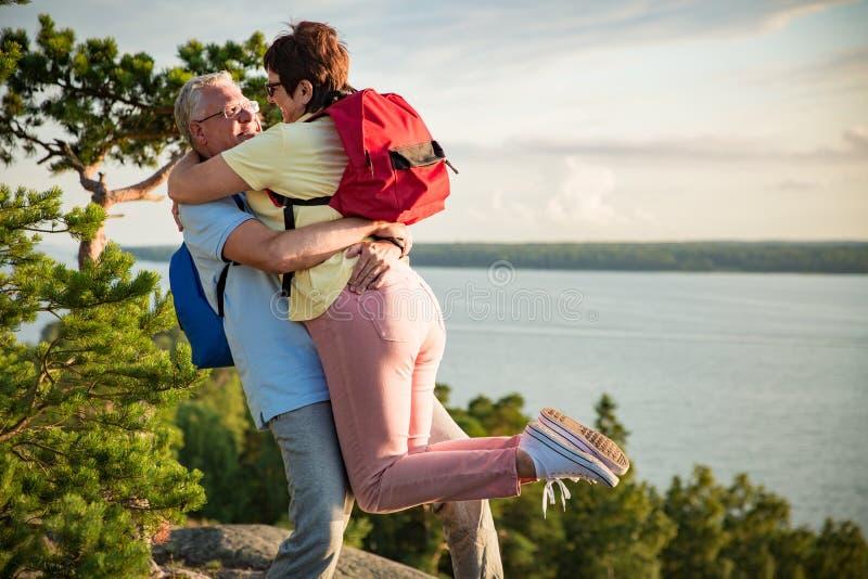 El caminar mayor cariñoso de los pares, colocándose en el top de la roca imagenes de archivo