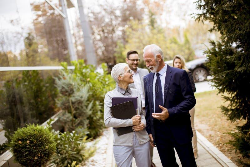 El caminar mayor y joven de los empresarios al aire libre foto de archivo libre de regalías