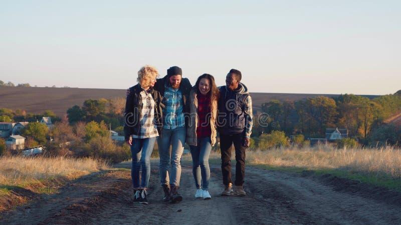 El caminar multirracial de cuatro amigos abrazado fotos de archivo