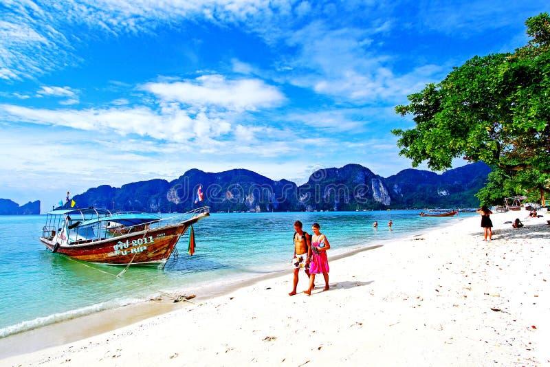 El caminar precioso de los pares y relajación en la playa blanca de la arena y el barco de la cola larga con el fondo del cielo a imagen de archivo