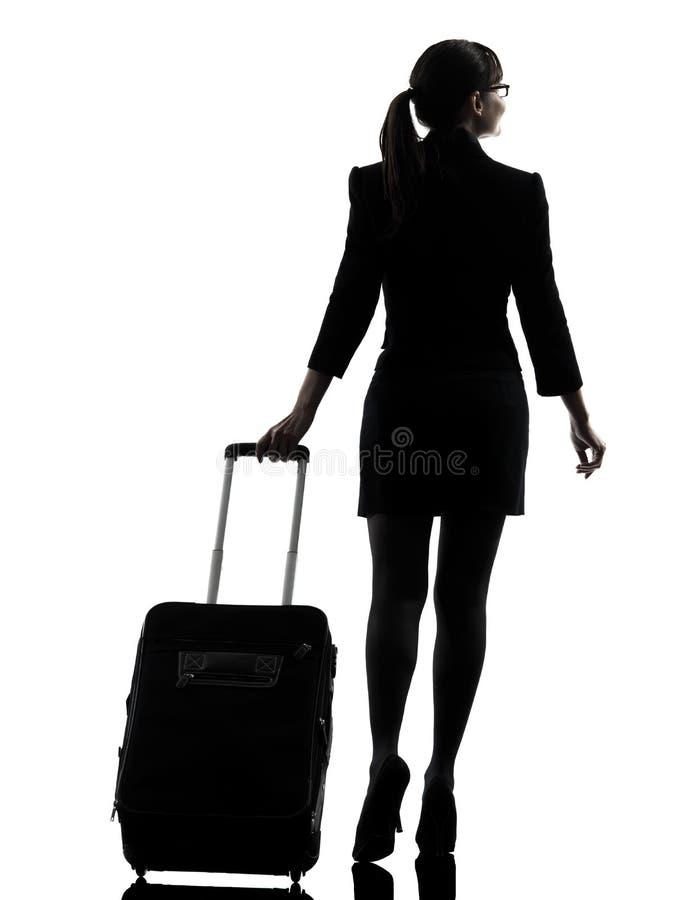 El caminar que viaja de la mujer de negocios de la vista posterior   silueta foto de archivo