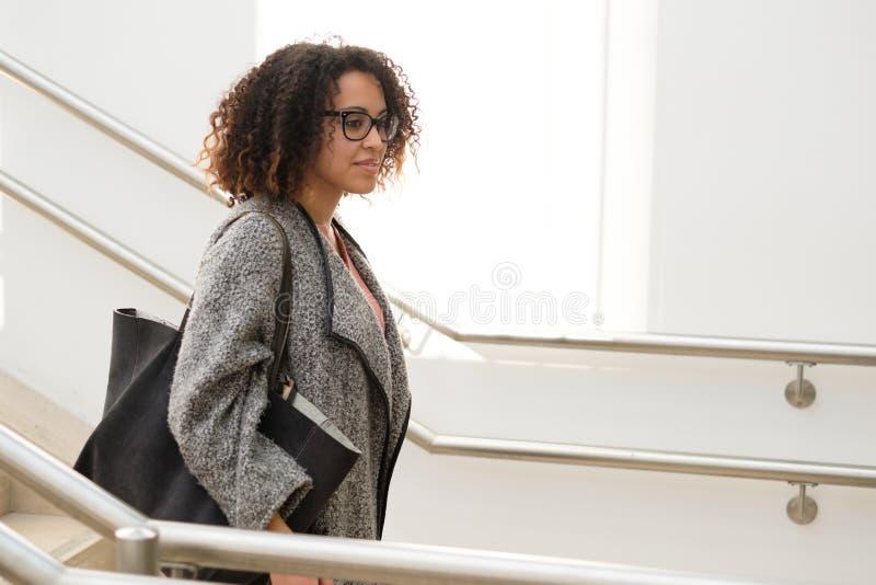El caminar vestido casual del pozo de la mujer negra en la ciudad fotografía de archivo