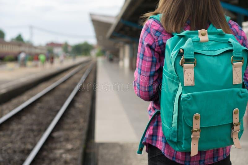 El caminar y las esperas de la mujer del viajero entrenan en la plataforma ferroviaria, llamarada de la luz de Sun, foco selectiv imagen de archivo