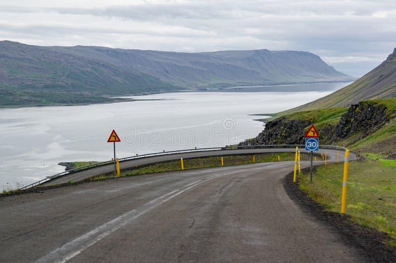 El camino en declive de enrrollamiento peligroso con peligro señal adentro Islandia con un efecto de la falta de definición de mo imagen de archivo