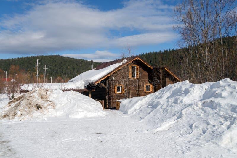 El camino nevoso lleva a una casa de madera entre las nieves acumulada por la ventisca contra la perspectiva del taiga imagen de archivo