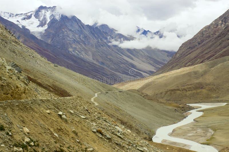 El camino sigue un alto del río en las montañas fotos de archivo libres de regalías