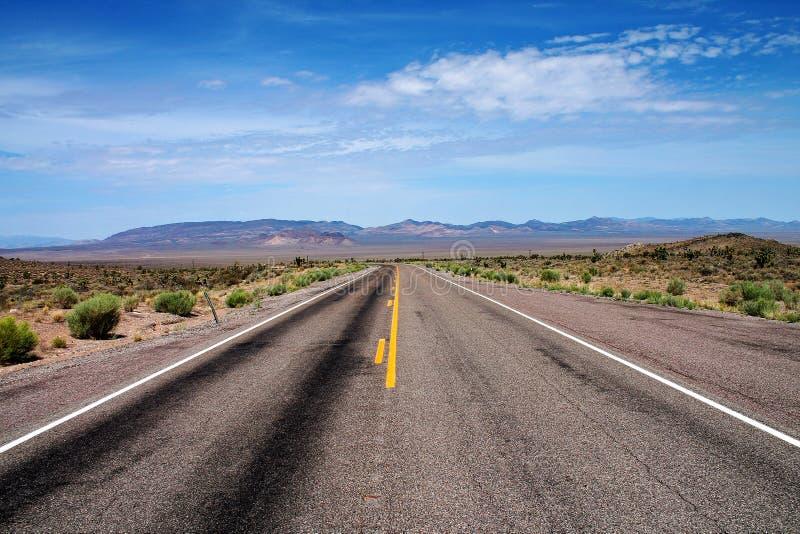 El camino vacío del desierto con friega arbustos y las montañas distantes en Nevada imágenes de archivo libres de regalías