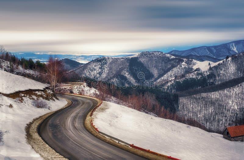 El camino vacío que viene a través de las montañas del invierno foto de archivo libre de regalías