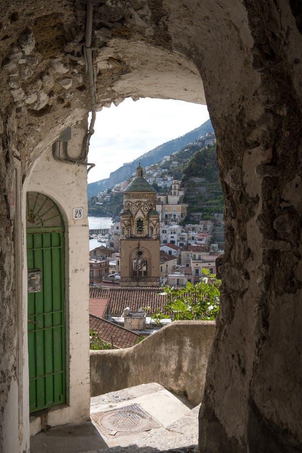 El campanario de la catedral de Amalfi, visto a través el arco de un alto del callejón para arriba en la ladera de la costa de Am imagenes de archivo