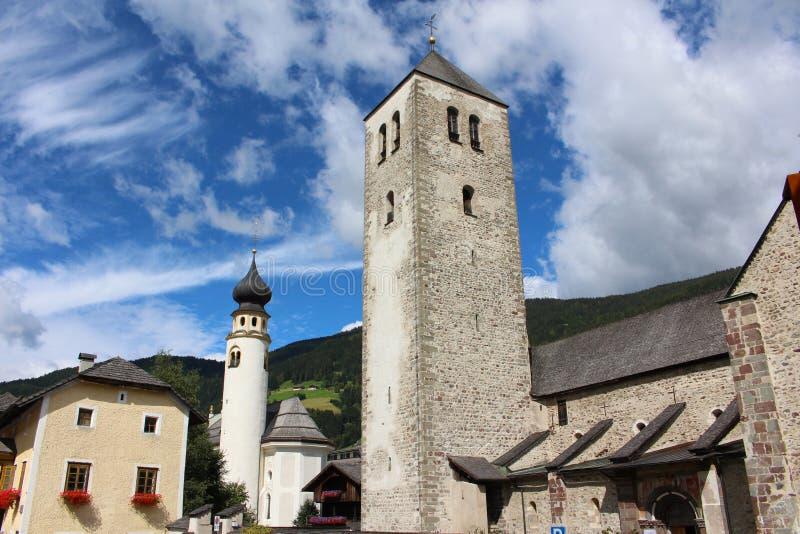 El campanario de la iglesia colegial de San Cándido y de que de la iglesia de San Micaela, San Cándido, dolomías, Italia fotografía de archivo