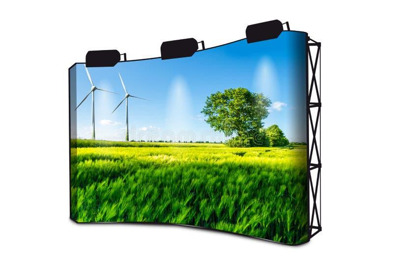 El campo de trigo verde con el árbol, el cielo azul y el viento rueda en el fondo - turbinas de viento que generan electricidad - foto de archivo