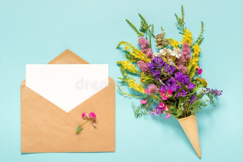 El campo del ramo coloreó las flores en cono de helado de la galleta y sobre del arte con la tarjeta de papel en blanco vacía par imágenes de archivo libres de regalías