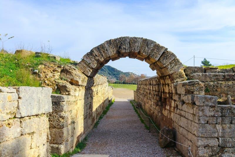 El campo donde las Olimpiadas originales fueron llevadas a cabo vistas con las ruinas del arco a través del cual los atheletes gr imagenes de archivo