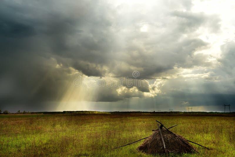 El campo sin fin con el bosque en el horizonte y el cielo tempestuoso hermoso con los rayos de detrás las nubes Pajar en el fi fotos de archivo