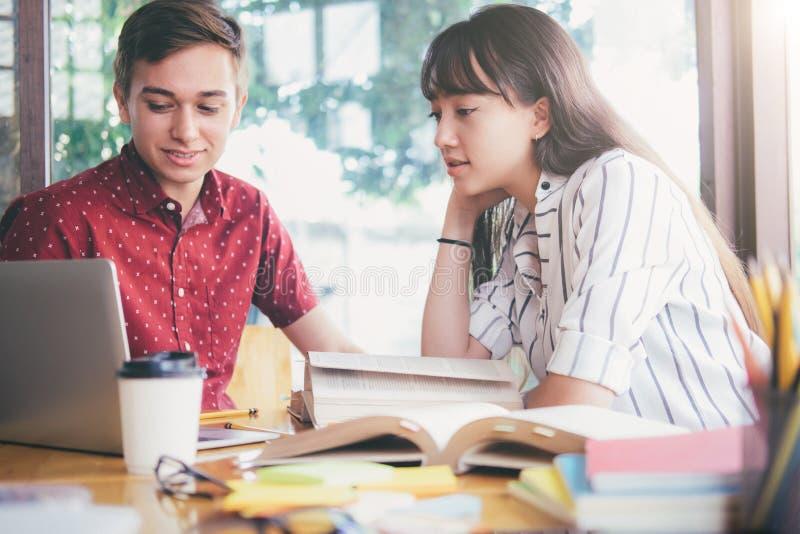 El campus joven de los estudiantes ayuda al amigo que alcanza y que aprende imagen de archivo libre de regalías