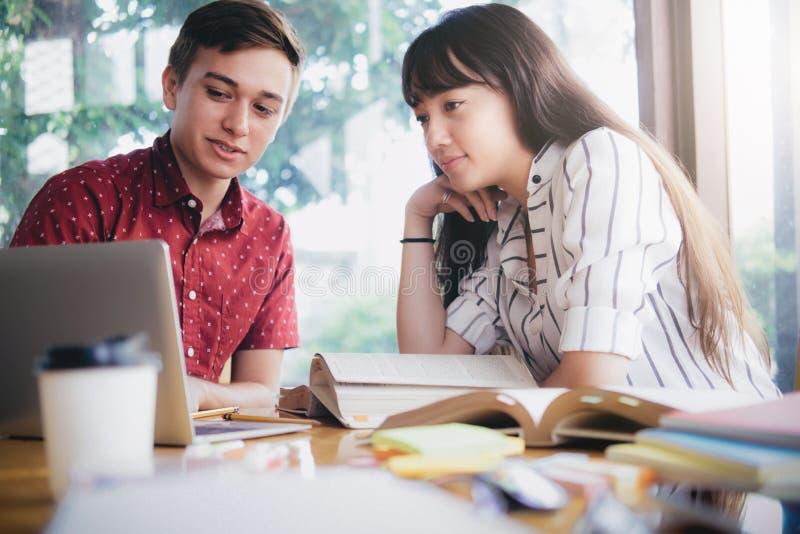 El campus joven de los estudiantes ayuda al amigo que alcanza y que aprende imagenes de archivo