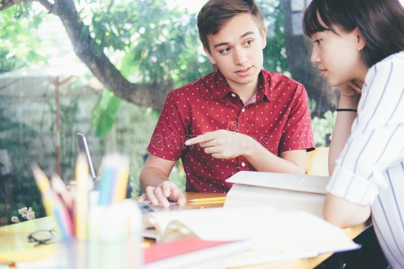 El campus joven de los estudiantes ayuda al amigo que alcanza y que aprende fotos de archivo libres de regalías