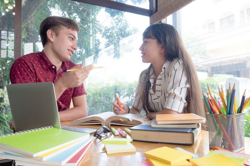 El campus joven de los estudiantes ayuda al amigo que alcanza y que aprende fotos de archivo