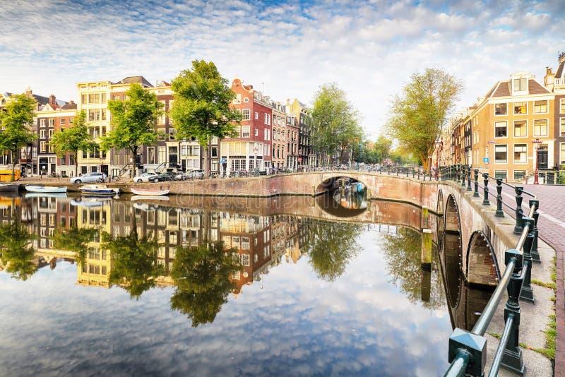 El canal de Amsterdam contiene las reflexiones vibrantes, Países Bajos, panora foto de archivo