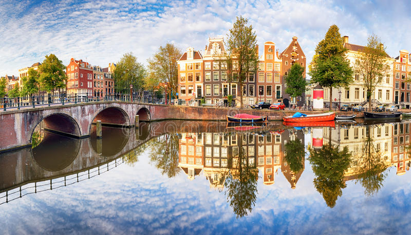 El canal de Amsterdam contiene las reflexiones vibrantes, Países Bajos, panora imágenes de archivo libres de regalías