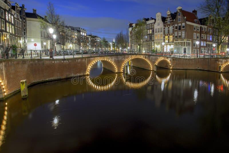 El canal de Amsterdam en la noche foto de archivo