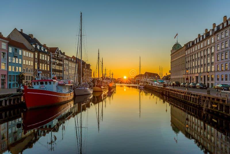El canal de Copenhague Nyhavn y la salida del sol sobre el agua tranquila y los barcos que reflejan en la superficie imagen de archivo libre de regalías