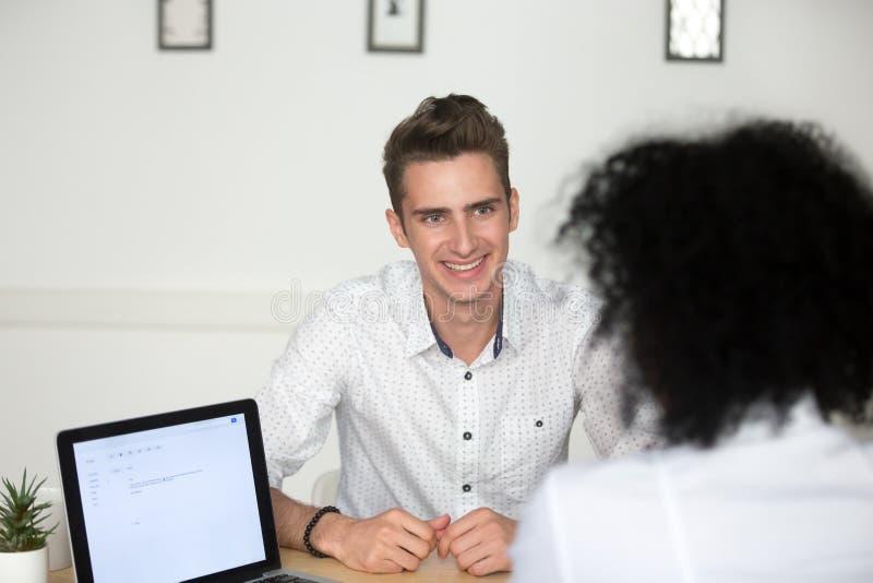 El candidato de trabajo sonriente que contesta feliz al reclutador pregunta durin fotos de archivo libres de regalías