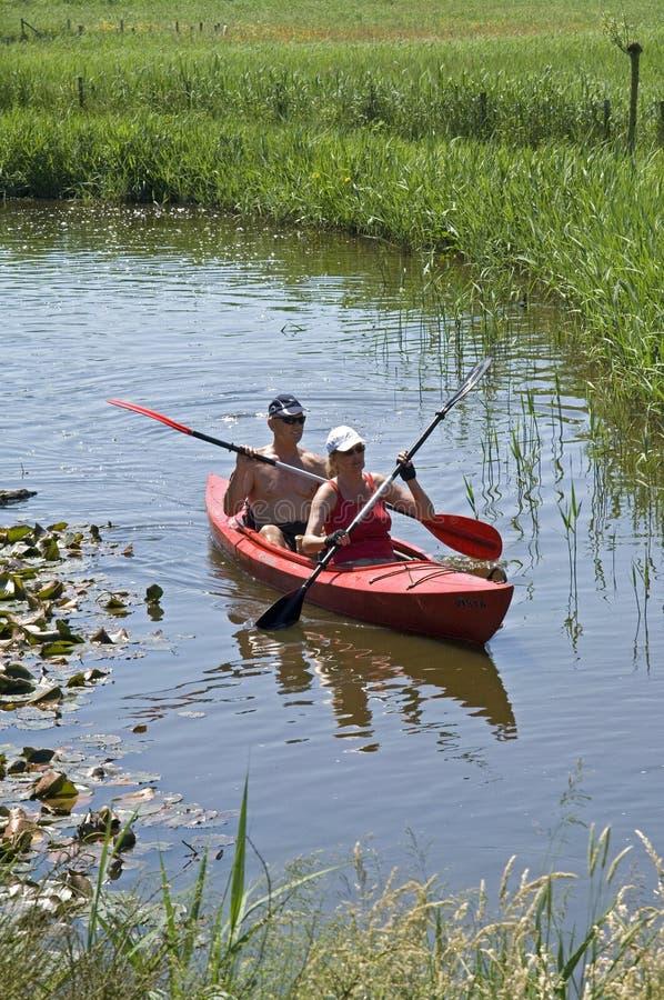 El Canoeing en el campo en un canal estrecho foto de archivo