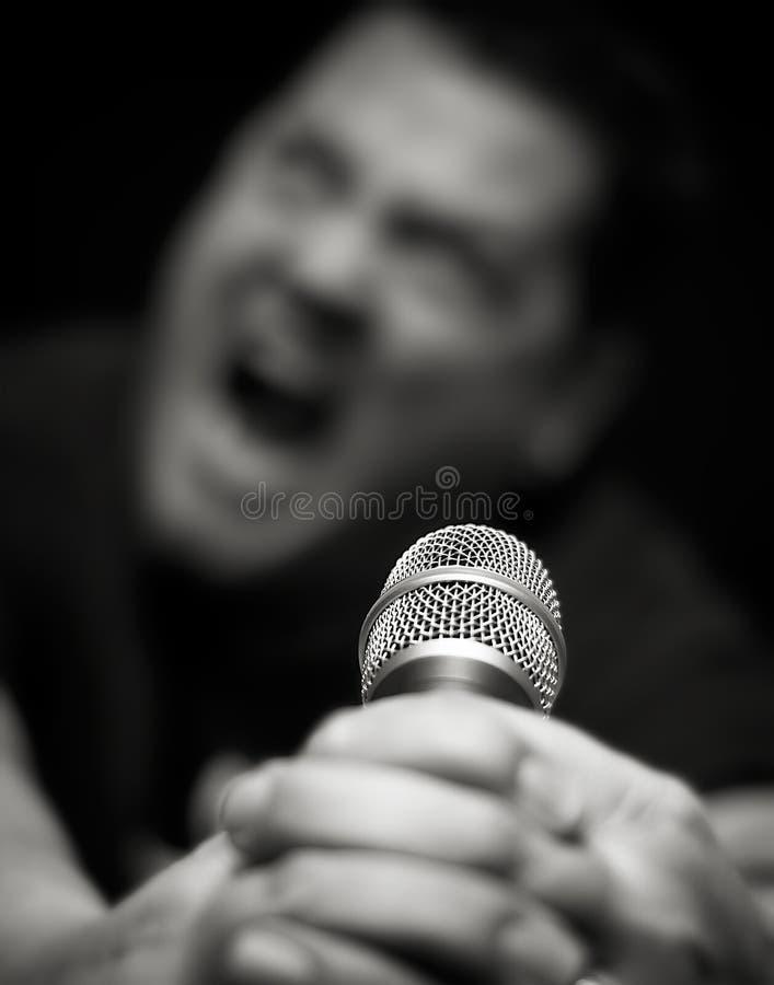 El cantante de metales pesados de sexo masculino grita en el micrófono foto de archivo libre de regalías