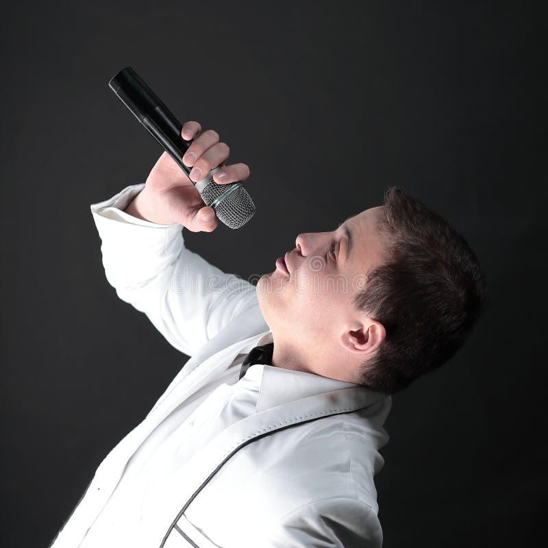 El cantante hermoso del hombre realiza una canción Aislado en negro foto de archivo