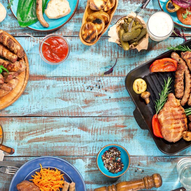 El capítulo de la comida asó a la parrilla en la tabla de madera el día soleado imagenes de archivo