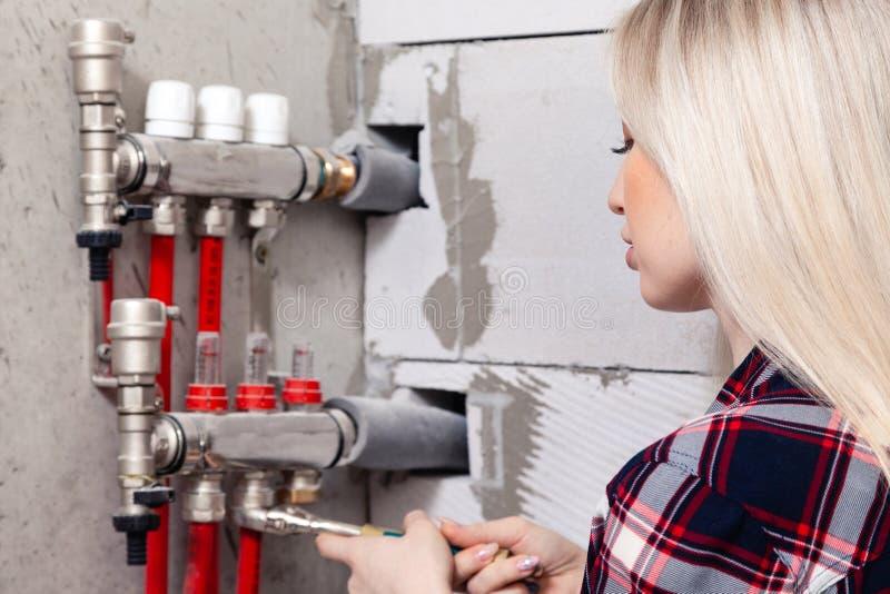 El capataz rubio de la muchacha aprieta las nueces con la llave en sistema de control de piso caliente del agua en casa bajo cons fotos de archivo