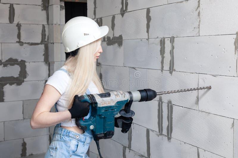 El capataz rubio de la muchacha del primer en el casco blanco de la construcción que sostiene el perforador profesional, perfora  fotografía de archivo libre de regalías