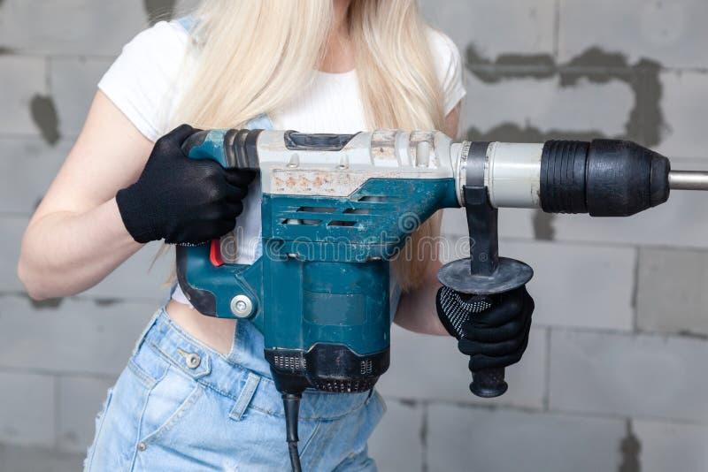 El capataz rubio de la muchacha del primer en el casco blanco de la construcci?n que sostiene el perforador profesional, perfora  fotografía de archivo