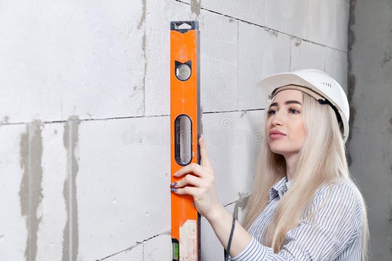 El capataz rubio del diseñador de la muchacha del primer en el casco blanco de la construcción mide el nivel constructivo anaranj foto de archivo libre de regalías