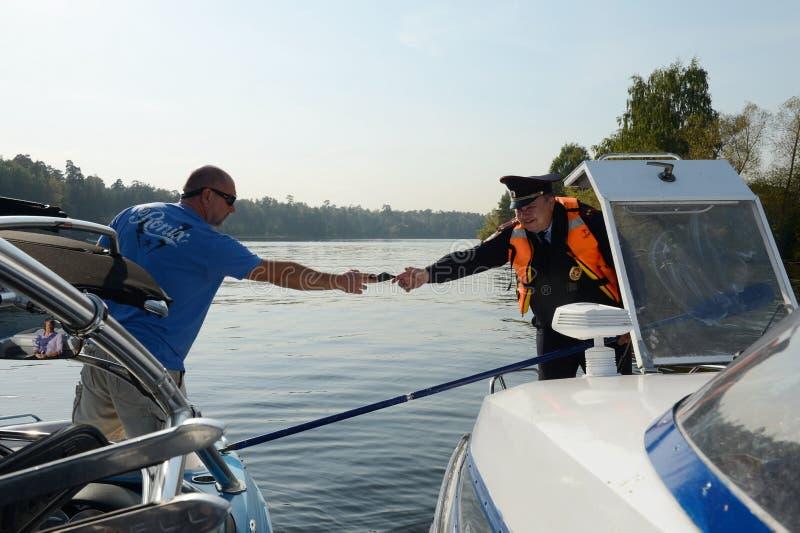 El capitán de un pequeño buque transmite los documentos a un oficial de policía fotos de archivo libres de regalías