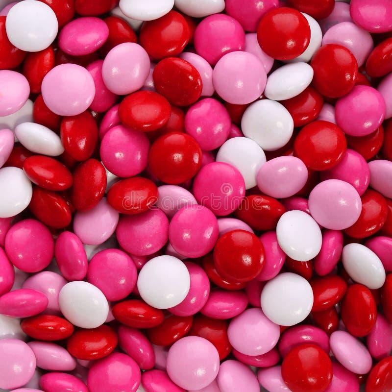 El caramelo de la tarjeta del día de San Valentín colorida del chocolate cubrió en el rosa, rojo foto de archivo libre de regalías