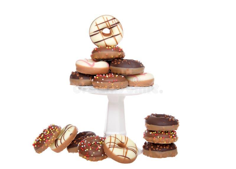 El caramelo miniatura cubrió los anillos de espuma apilados en el pedestal aislado en blanco foto de archivo