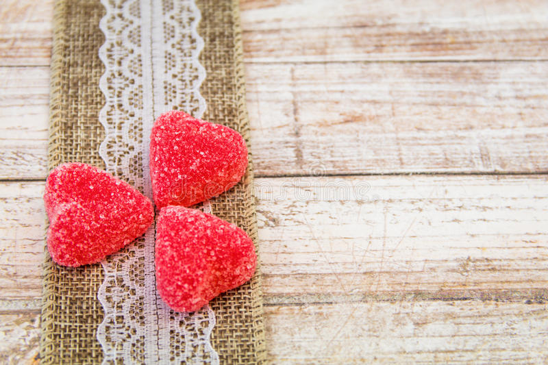 El caramelo y la arpillera rojos del corazón atan en el tablero de madera fotografía de archivo
