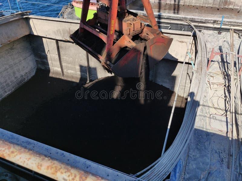 El carbón del lanzamiento del gancho agarrador de la grúa en la gabarra, descargando la operación fotos de archivo libres de regalías