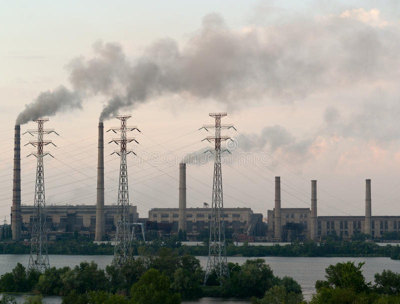 El carbón encendió la estación de la energía eléctrica al lado de un río imágenes de archivo libres de regalías