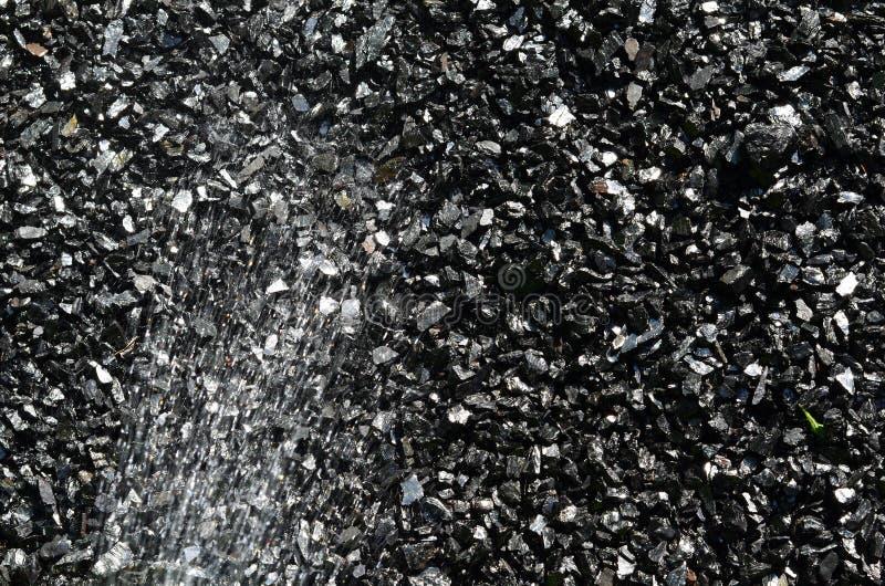 El carbón se moja con agua para reducir el polvo imagen de archivo